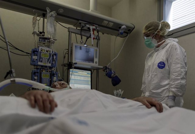 Personal sanitario totalmente protegido atiende a un paciente ingresado en la Unidad de Cuidados Intensivos del Hospital Infanta Sofía en San Sebastián de los Reyes