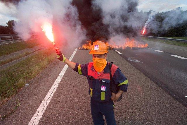 Un trabajador de Alcoa San Cibrao enciende una bengala durante una manifestación en la que han cortado la Autopista A6 con la quema de neumáticos, en Outeiro de Rei, Lugo, Galicia (España), a 22 de septiembre de 2020.