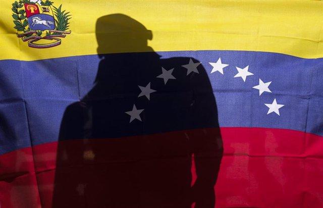 Un hombre detrás de una bandera de Venezuela.