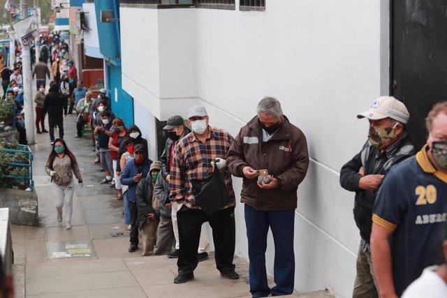 Un grupo de personas espera su turno parapoder acceder a una entidad bancaria en Liam, Perú, en el marco de la crisis sanitaria provocada por la COVID-19.