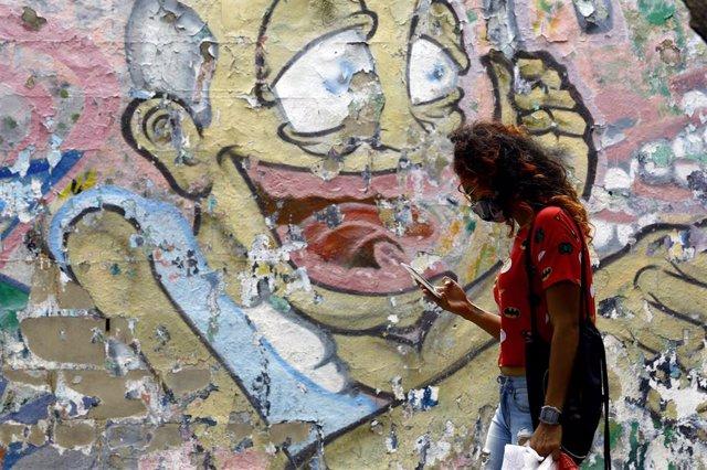 Una mujer pasea por una calle de Caracas