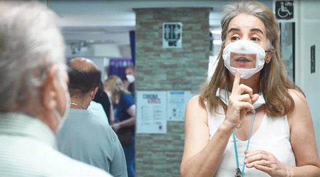 Una mujer utiliza una mascarilla transparente que facilita la lectura de labios