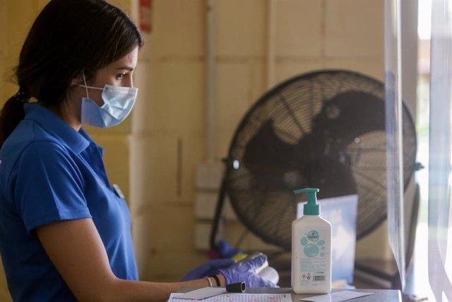 Una trabajadora se protege con mascarilla y gel desinfectante