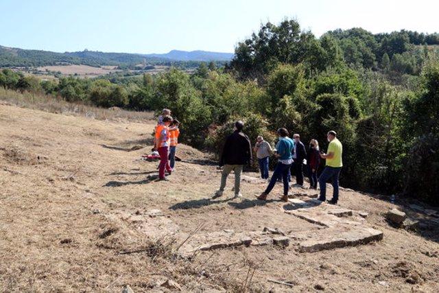 En primer pla restes de les parets de la casa residencial de la vil·la romana de Llorís i al fons els arqueòlegs explicant el jaciment el dia 30 de setembre del 2020. (horitzontal)