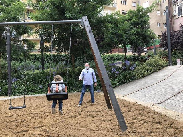 Una niña y su abuelo juegan en los columpios