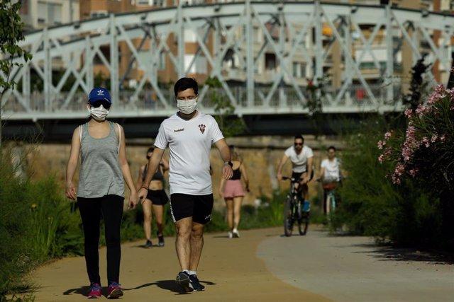 Personas haciendo deporte y paseando por la mota del río a su paso por Murcia