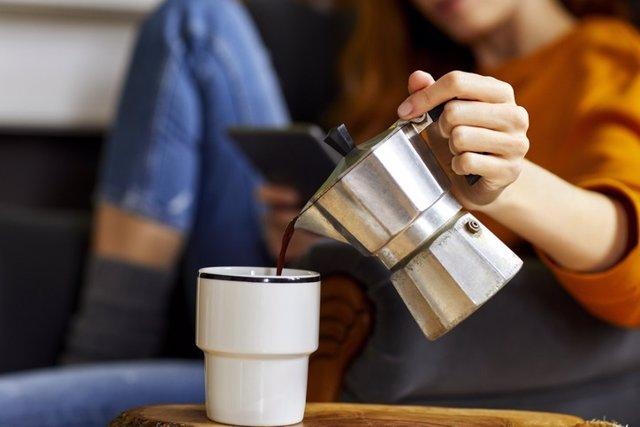 Mujer joven vertiendo café en la taza en casa con una cafetera