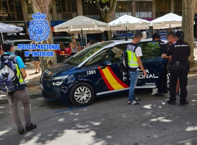 Un vehicle i agents de la policia espanyola, detenint el propietari d'un 'kebab' al passeig de l'Estació de Valls per explotació laboral de compatriotes seus. Imatge publicada l'1 d'octubre del 2020. (Horitzontal)