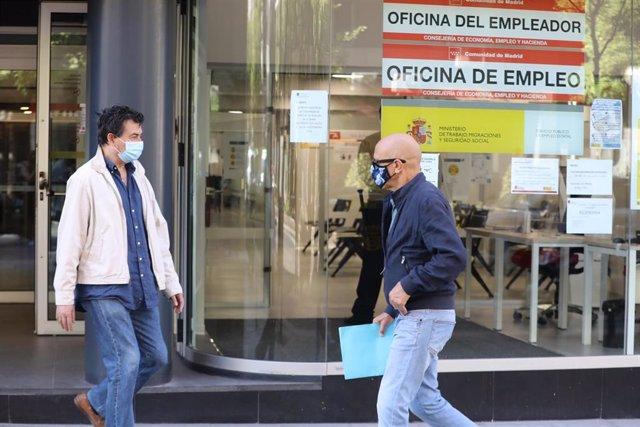 Un hombre con mascarilla pasa por una oficina de empleo de Madrid (España)