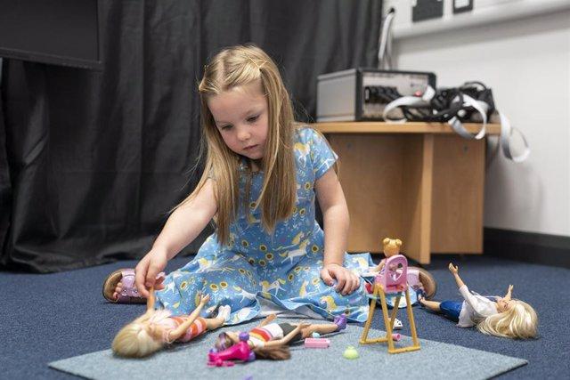 Niña jugando con muñecas
