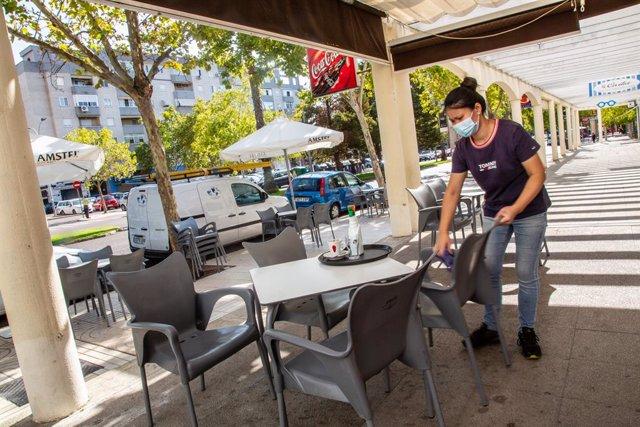 Una camarera limpia una de las mesas de la terraza del bar