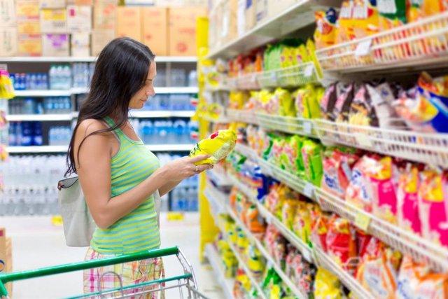Mujer comprando patatas fritas en un supermercado. Alimentos procesados.