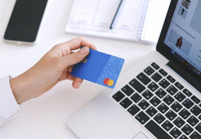Una persona utilizando su tarjeta de crédito para realizar compras online con un ordenador
