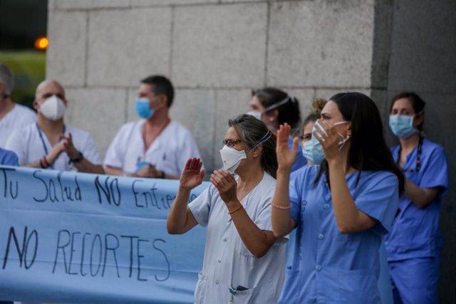Personal sanitario del Hospital Clínico San Carlos de la Comunidad de Madrid aplaude durante la primera protesta de la desescalada con concentraciones en hospitales y centros de salud. Los sanitarios se han manifestado en esta ocasión no para recibir apla