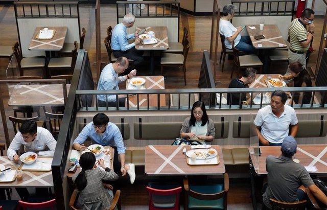 Un grupo de personas come en un restaurante de Hong Kong siguiendo las normas de distanciamiento social impuestas para evitar más contagios por coronavirus.