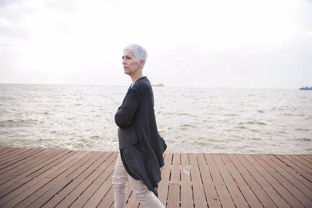 Mujer mayor paseando por la orilla de la playa.
