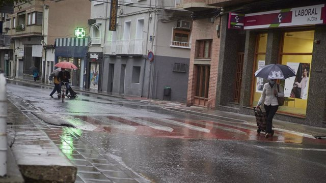 Vecinos del municipio de San Adrián caminan protegidos con un paraguas, Navarra (España), a 2 de octubre de 2020.