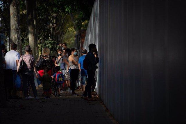 Padres y alumnos esperan a las puertas de un colegio durante el primer día del curso escolar 2020-2021, en Barcelona, Catalunya (España), a 14 de septiembre de 2020.