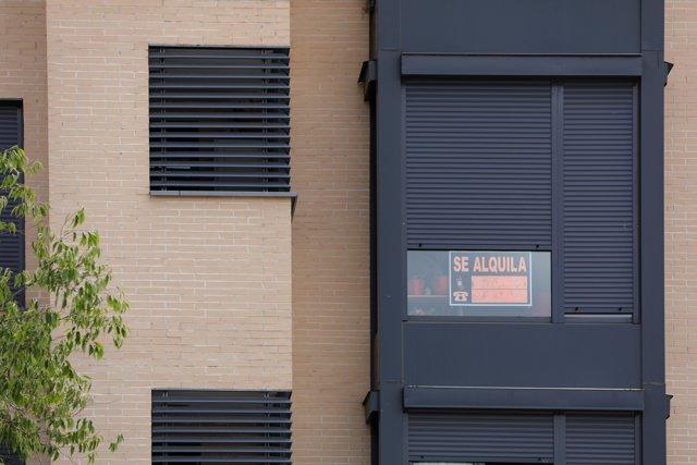 En la fachada de un edificio se ve un cartel de Se Alquila bajo la persiana de uno de los pisos