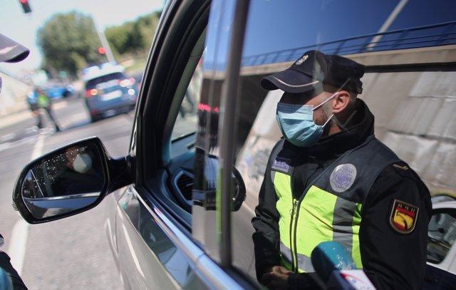 Un policía de la Unidad de Prevención y Reacción para a un coche en un control policial en la Avenida de los Poblados con la A-42 de entrada a Madrid, la mañana del 3 octubre del 2020