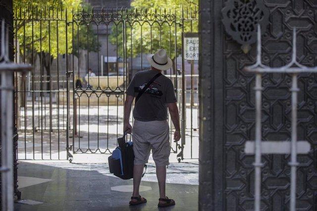 Un turista observa el Patio de los Naranjos desde la salida de la Catedral. En Sevilla (Andalucía, España), a 27 de agosto de 2020.