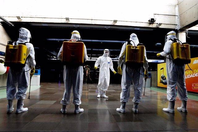Soldados brasileños con trajes protectores frente al coronavirus en Sao Paulo realizan labores de desinfección.