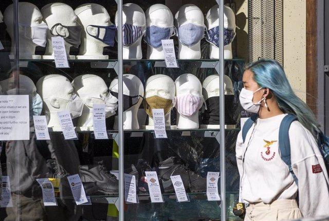 Una mujer con mascarilla pasa ante una tienda de mascarillas en Edimburgo