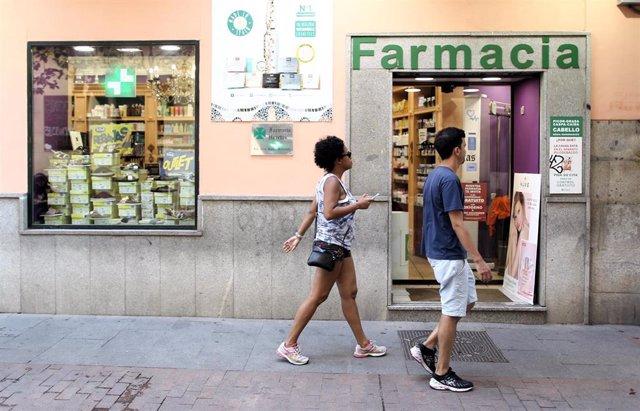 Una pareja cruza por delante de la puerta principal de una farmacia.