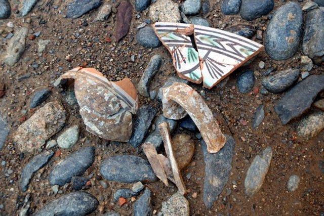 Detall de ceràmica localitzada al jaciment medieval de la Plaça de les Monges de la Seu d'Urgell i un os decorat. Imatge del 5 d'octubre del 2020. (horitzontal)