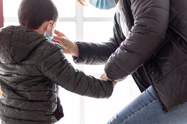Una madre coloca a su hijo una mascarilla