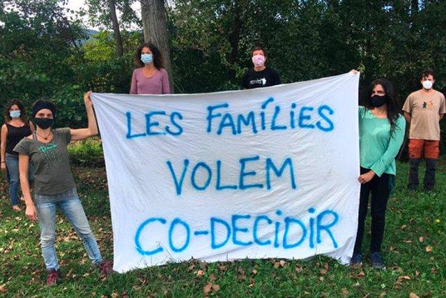 Pla general de diversos pares i mares d'alumnes de l'escola de Mieres aguantant una pancarta per demanar decidir conjuntament les mesures de les escoles el 30 de setembre de 2020 (Horitzontal)