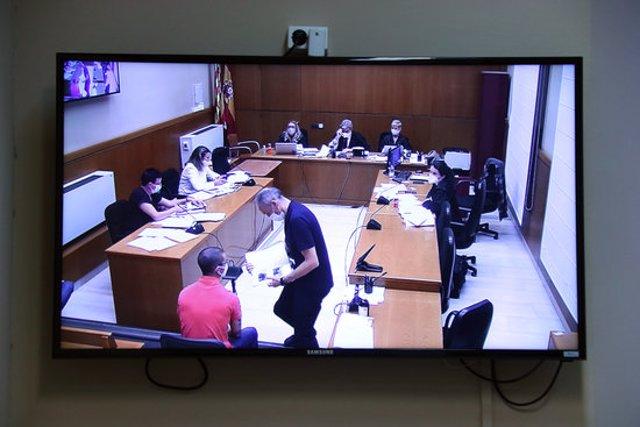 Un acusat comprova la seva presència en una foto durant el judici contra tres acusats de desordres públics i atemptat el gener del 2018 a la Ciutadella, en una fotografia de la pantalla de la sala de premsa del TSJC. (Horitzontal)