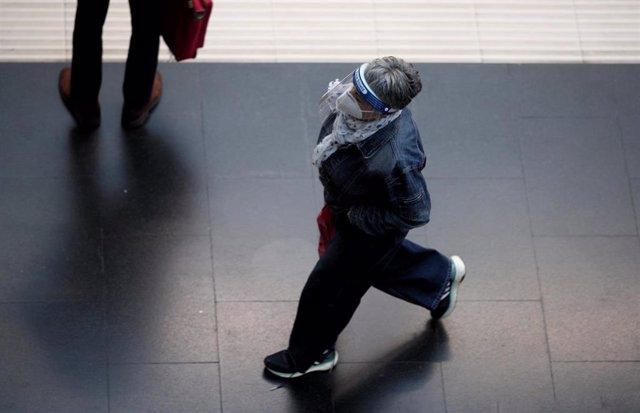Una mujer protegida con pantalla protectora y mascarilla camina por un andén de la Estación de Tren Príncipe Pío durante el primer día laborable con restricciones de movilidad en toda la capital de Madrid (España), a 5 de octubre de 2020.