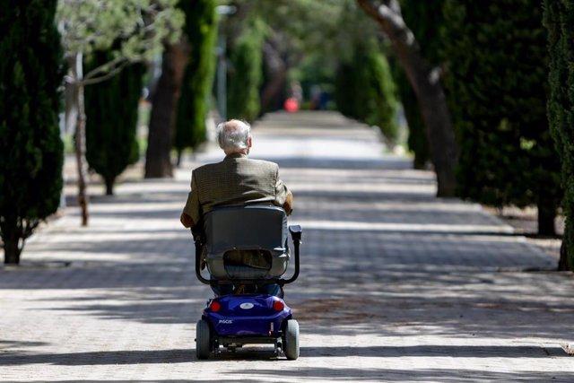 Un anciano en silla de ruedas eléctrica en un parque, en Madrid (España), a 2 de mayo de 2020. .