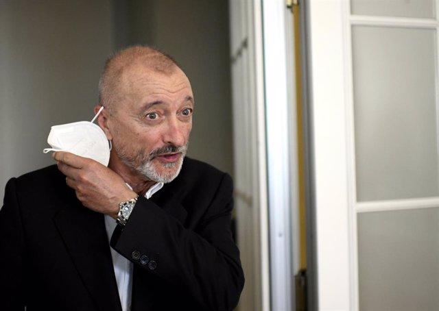 El escritor Arturo Pérez-Reverte se quita la mascarilla a su llegada a la presentación de su libro 'Línea de fuego' en el Hotel Westin Palace,