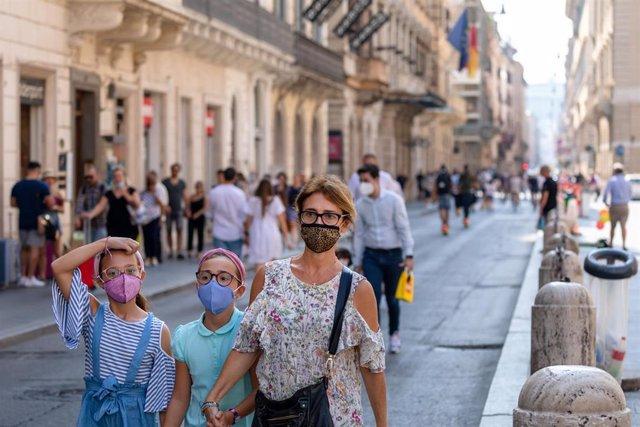 Una familia pasea con mascarilla por Roma