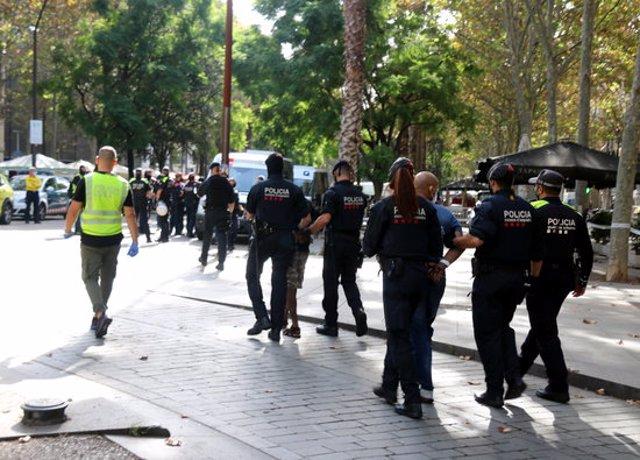 Pla mitjà de diversos detinguts al Raval conduïts caminant per mossos d'Esquadra, el 7-10-20 (horitzontal).