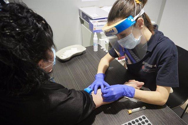 Una trabajadora sanitaria realiza una extracción de muestras en el recinto ferial REFENA de Pamplona