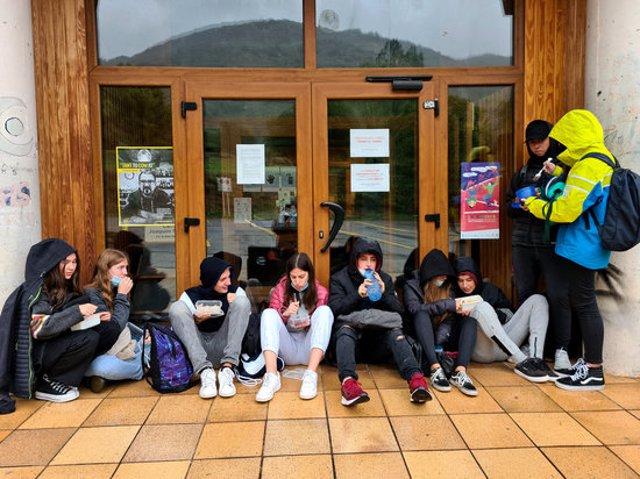 Pla general d'un grup de joves dinant amb carmanyola a la porta de l'Arxiu Comarcal del Pallars Sobirà on es resguardaven de la pluja el 2 d'octubre del 2020. (horitzontal)
