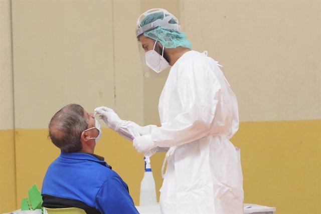 Una sanitaria toma muestras a un hombre a través de un frotis de nariz durante la realización de test de antígenos, foto de archivo