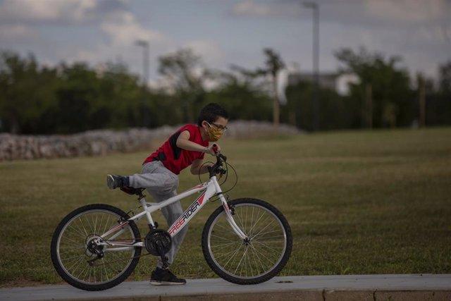 Un niño protegido con mascarilla monta en bicicleta en el tercer día de desconfinamiento de niños y preadolescentes durante el estado de alarma por la crisis del coronavirus en el que los menores de 14 años pueden salir durante una hora, de 09:00 a 21:00