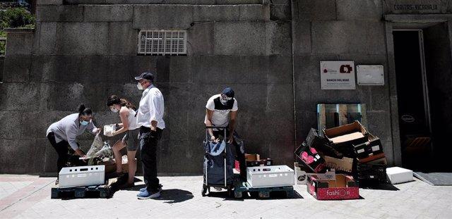 Dos personas recogen alimentos que les dan dos voluntarios a las puertas de la Parroquia Santa María Micaela, en Madrid, el pasado 29 de mayo, en pleno confinamiento por coronavirus.