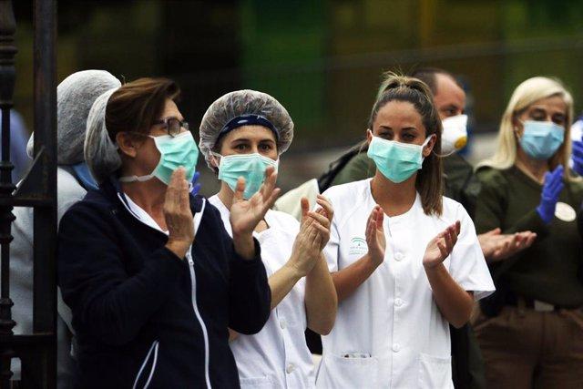 Bomberos realizan junto a trabajadores de Correos el aplauso a los sanitarios en la puerta principal del Hospital Regional de Málaga el 8 de abril 2020.