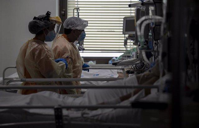 Dos sanitarios atienden a un paciente en la Unidad de Cuidados Intensivos (UCI) dedicada a enfermos de coronavirus del Hospital Universitario Ramón y Cajal, en Madrid (España), a 8 de octubre de 2020. Durante esta segunda oleada de la pandemia en España,