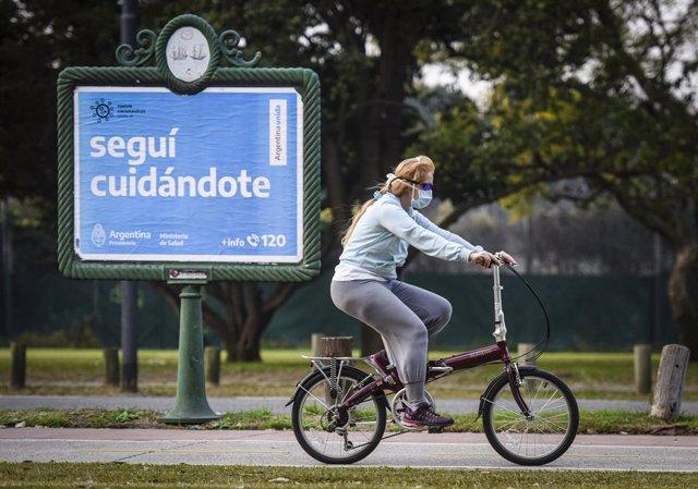 Una mujer pasea en bicicleta por Buenos Aires.