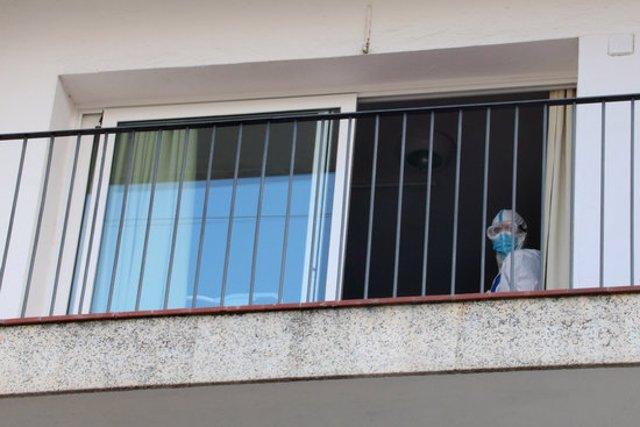Detall del balcó d'una habitació de la residència Calafell Park de Segur de Calafell, amb un treballador amb EPI sortint per la porta. Imatge del 9 d'octubre del 2020 (horitzontal)