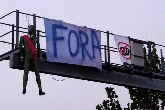 El maniquí que representa Felip VI amb els dos cartells en contra del Rei penjant aquest 9 d'octubre del 2020 al matí del radar de tram a Cassà de la Selva (Horitzontal)