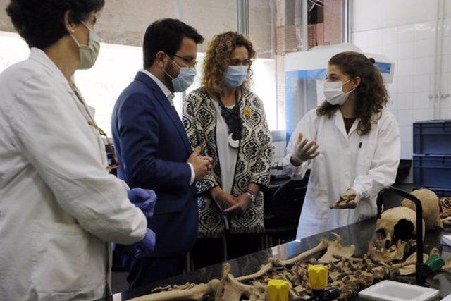 Pla tres quarts de la consellera Capella i el vicepresident Aragonès escoltant les explicacions de les investigadores al laboratori de la UAB. Imatge del 9 d'octubre del 2020. (Horitzontal)
