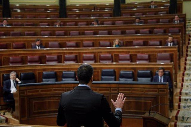 El presidente del Gobierno, Pedro Sánchez (de espaldas), interviene en el Congreso con los ministros Fernando Grande-Marlaska y Salvador Illa en el hemiciclo