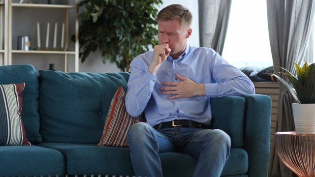 Hombre con tos crónica sentado.